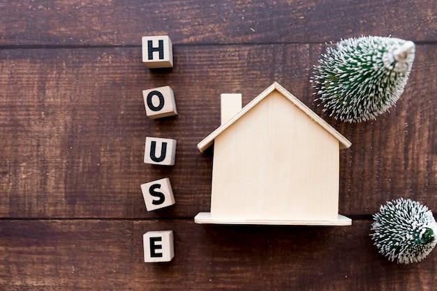 Bloques de letras de la casa cerca del modelo de finca con dos árboles de navidad sobre fondo de madera con textura