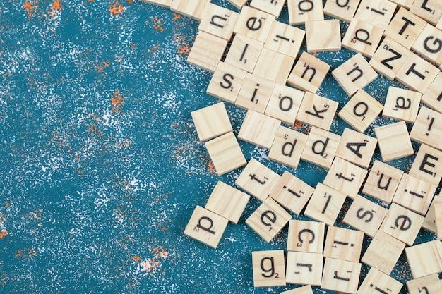 Bloques de letras hechos de madera y aislados en la superficie del patrón azul