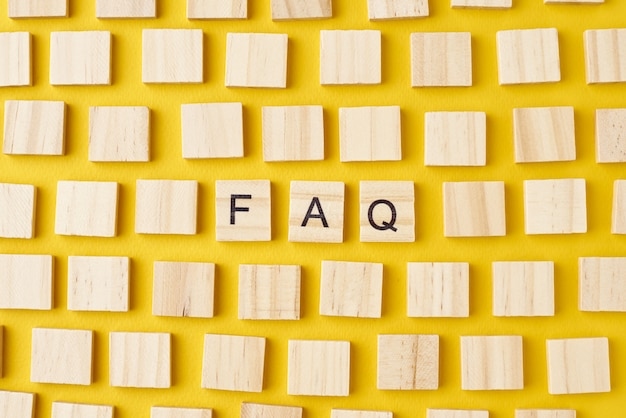 Bloques de madera con abreviatura preguntas frecuentes sobre fondo amarillo, vista superior
