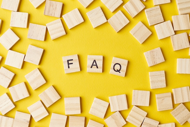 Bloques de madera con abreviatura preguntas frecuentes sobre fondo amarillo