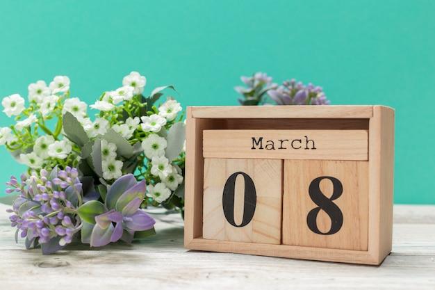 Bloques de madera en caja con fecha y flores.
