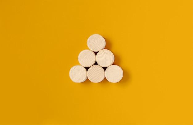 Los bloques de madera circulares se colocan sobre un fondo amarillo, los bloques de madera están dispuestos en forma triangular. concepto de bloque de madera, pancarta con espacio de copia de texto, póster, plantilla de maqueta.