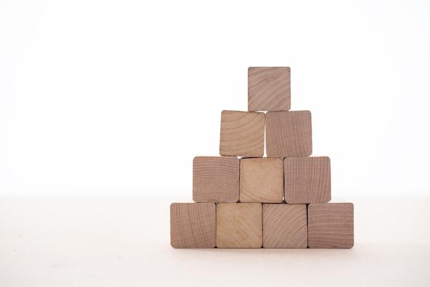 Los bloques de madera colocados sobre un fondo blanco representan la estabilidad de los negocios.