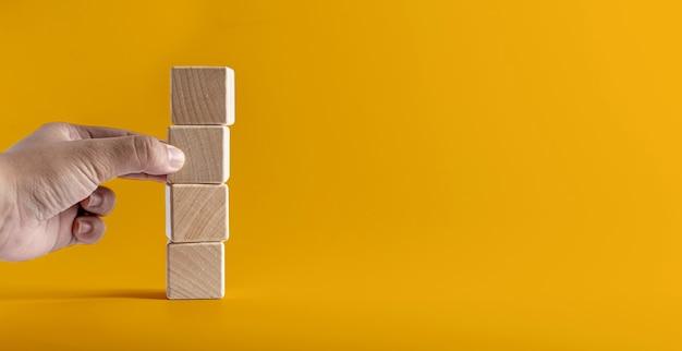 Bloques de madera cuadrados apilados uno contra el otro sobre un fondo amarillo, la mano está a punto de coger el tercer bloque de madera. banner de concepto de bloque de madera con espacio de copia de texto, cartel, plantilla de maqueta.