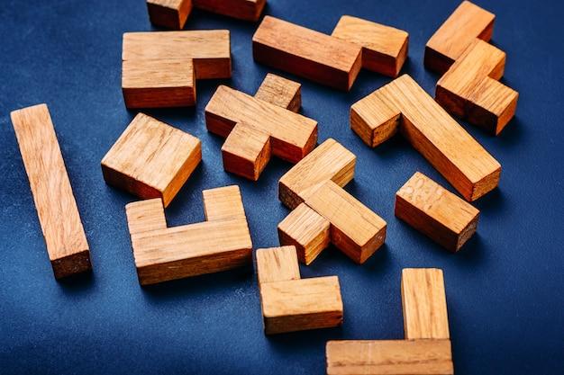 Bloques de madera de diversas formas geométricas en un fondo oscuro.