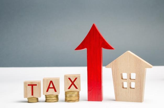 Bloques de madera con monedas y el impuesto de la palabra y una flecha hacia arriba junto a la casa. el concepto de crecimiento.