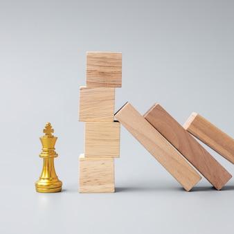 Bloques de madera o dominó cayendo a la figura dorada del rey del ajedrez. negocios, gestión de riesgos, solución, regresión económica, seguros