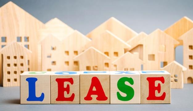 Bloques de madera con la palabra arrendamiento y casas en miniatura.