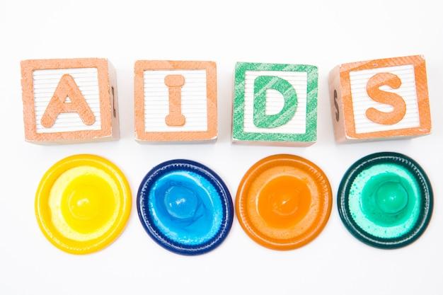 Bloques de madera que deletrean ayudas con cuatro condones.