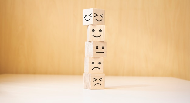 Bloques de madera con el símbolo de cara feliz sonrisa cara símbolo sobre la mesa, evaluación, aumento de calificación,