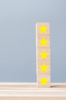 Bloques de madera con el símbolo de la estrella. opiniones de clientes, comentarios, calificación, clasificación y concepto de servicio.