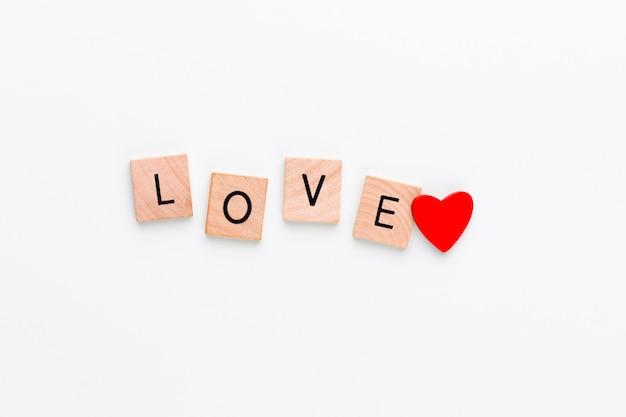 Bloques de madera en un tablero pastel con el corazón del final del texto.