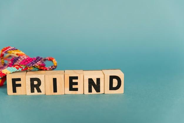 Bloques de madera con texto de amigos y pulseras multicolores.