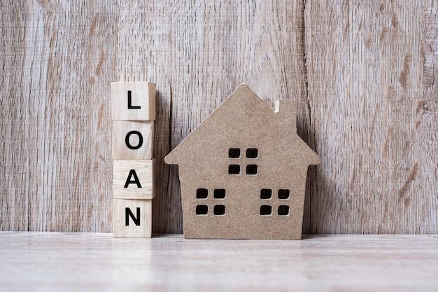 Bloques de madera con texto de préstamo y casa modelo de madera