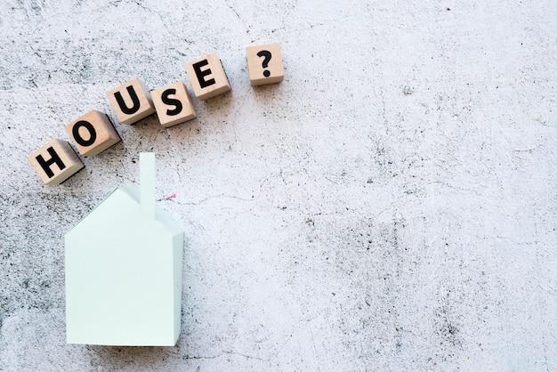 Los bloques del modelo de casa con signo de interrogación firman sobre el modelo de papel contra la pared blanca del grunge