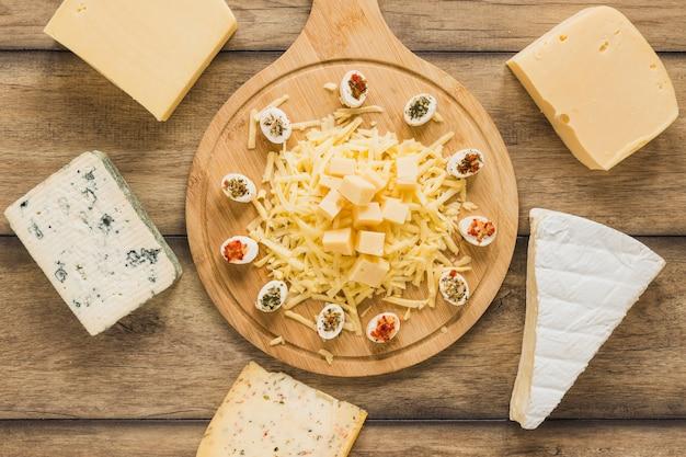 Bloques de queso rodeados cerca de la tabla de cortar de madera en el escritorio de madera