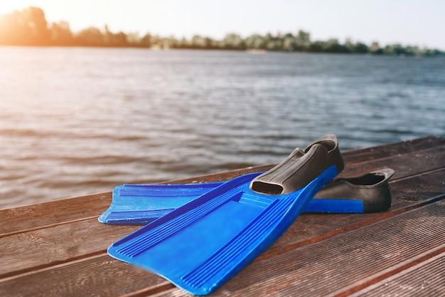 Blu aletas tumbado en la orilla del río arena. el sol brilla. río flotante naturaleza pura. el sol brilla. claro cielo azul.