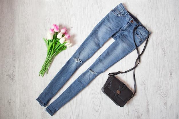 Blue jeans, bolso negro y ramo de tulipanes. concepto de moda