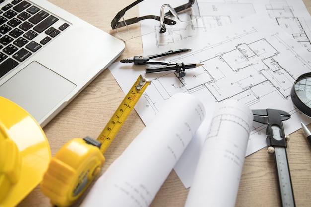 Blueprints y herramientas cerca de la computadora portátil