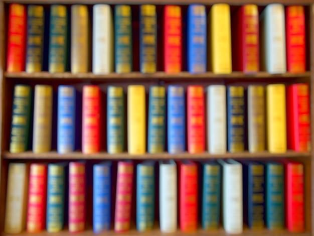 Blured de coloridos libros, libros de texto, literatura sobre madera estantería en la biblioteca.