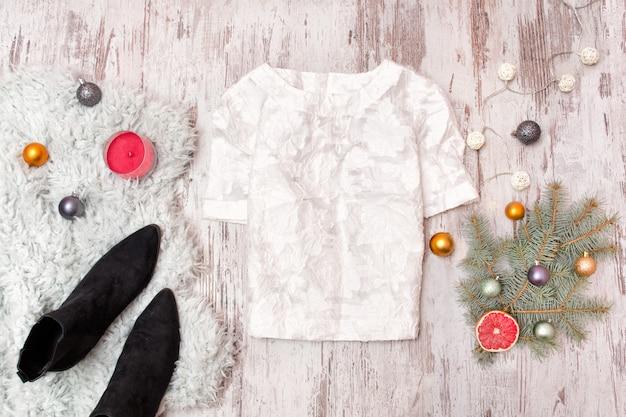 Blusa blanca, zapatos y rama de abeto decorado sobre fondo de madera.