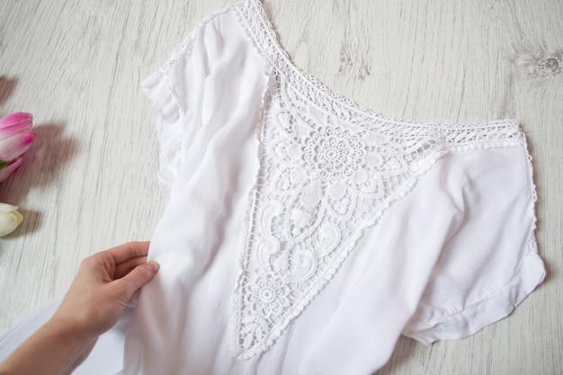 Blusa de encaje blanco en mano femenina.