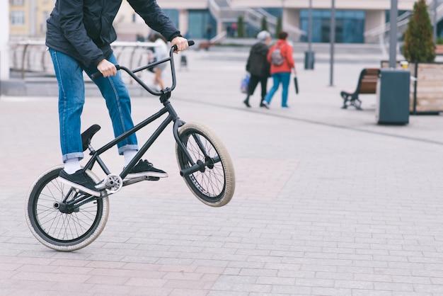 Bmx estilo libre. joven haciendo trucos en un parque en una bicicleta bmx. el ciclista entrena en la rueda trasera de la bicicleta.