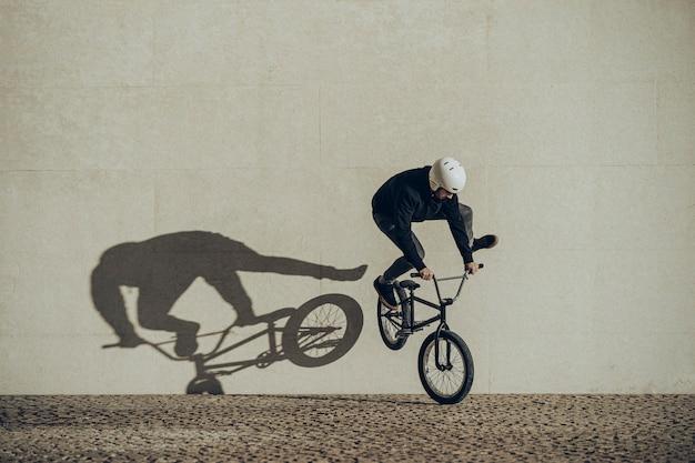 Bmx flatland rider haciendo un giro con su sombra proyectada en un muro de piedra