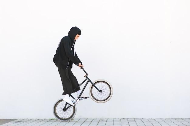 Bmx racer hace un truco en la pared blanca. jinete de bmx con una bicicleta en vuelo sobre blanco