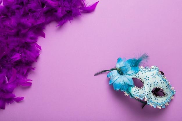 Boa de plumas morada con máscara de carnaval azul y espacio de copia