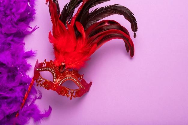 Boa de plumas morada con máscara roja de carnaval