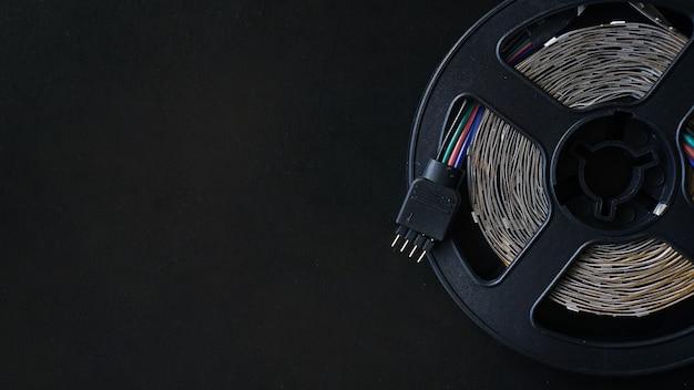 Bobina de cinta led. cinta de luces led sobre fondo negro. luz rgb apagada