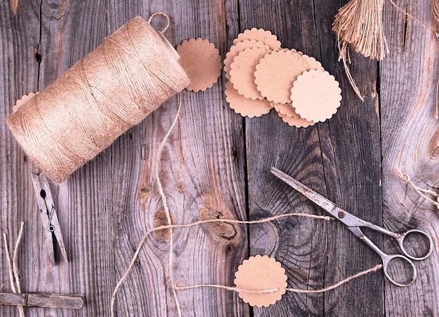 Bobina de cuerda marrón, etiquetas de papel y tijeras viejas
