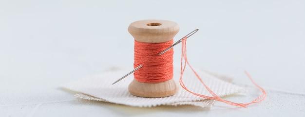 Bobina de madera de hilos de color coral para coser con una aguja sobre un fondo blanco, pancarta