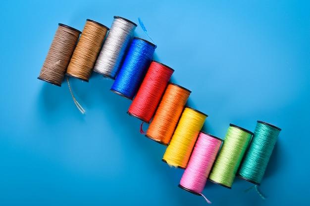 Bobinas de hilo de colores en la costura de la pared azul, lugar para el texto