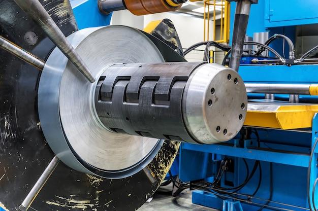 Bobinas industriales de chapa metálica conectadas con máquina perfiladora de chapa metálica.