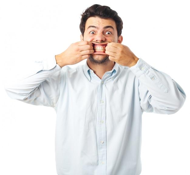 Boca de la apertura del hombre joven con las manos en un fondo blanco