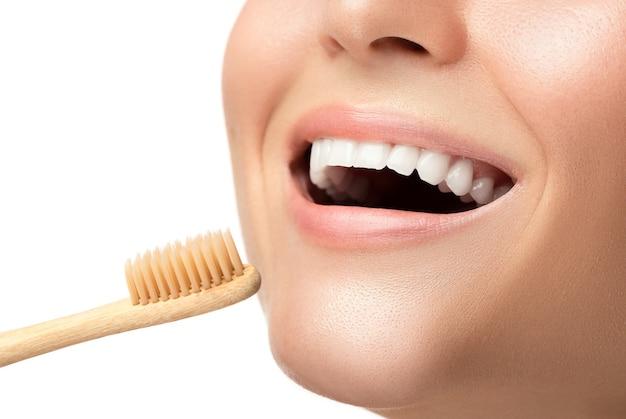 Boca femenina con dientes blancos y cepillo de dientes de bambú
