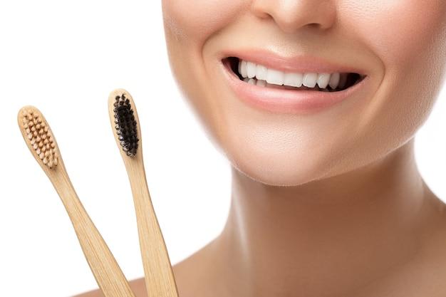 Boca femenina con dientes blancos y cepillos de dientes de bambú