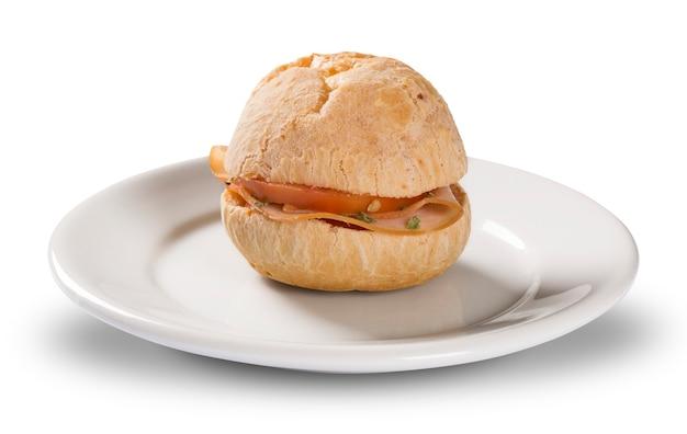 Bocadillo brasileño pao de queijo (pan de queso) en un plato blanco con queso, jamón, mantequilla