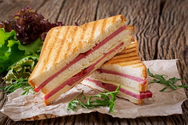 Bocadillo de club - panini con el jamón y el queso en fondo de madera. comida de picnic.