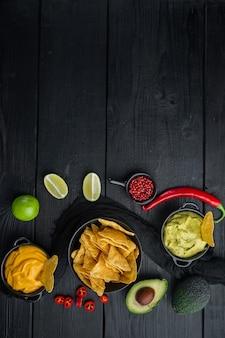 Bocadillo crujiente mexicano, nachos chips y salsas de aguacate guacamole de queso, sobre mesa de madera negra, vista superior o endecha plana