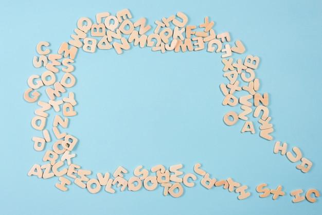 Un bocadillo de diálogo vacío hecho con letras de madera sobre fondo azul