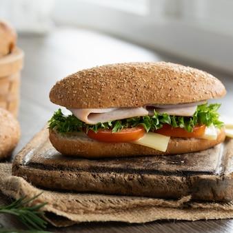 Bocadillo de jamón y queso con pan de sésamo y pan tostado en canasta.