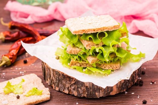 Un bocadillo de pan de cereal, hojas de lechuga y semillas de sésamo.