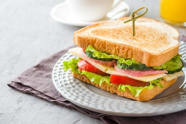 Bocadillo con queso, jamón y verduras frescas en una placa.