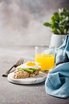Bocadillo saludable con aguacate fresco y huevos de codorniz fritos