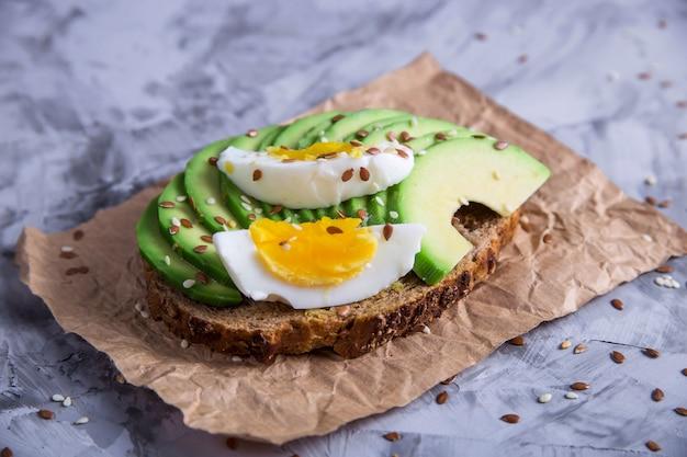Bocadillo sano hermoso - bocadillo del aguacate con el huevo. concepto de comida vegetariana