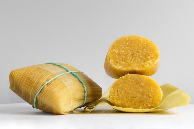 Bocadillo tradicional brasileño, pamonha, sobre fondo blanco.