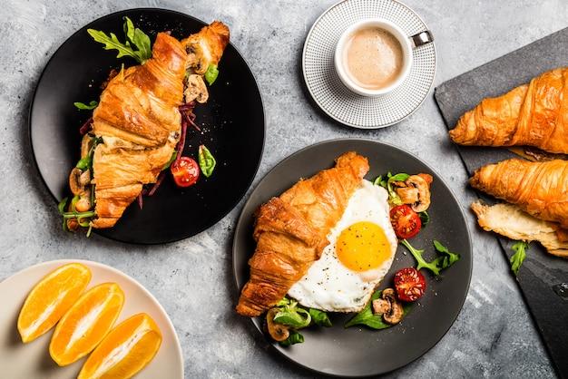 Bocadillos de croissant con huevo frito, hojas de ensalada